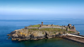 Ancient Castle on Island with Cliffs in the sea. Old Ancient Castle on the Island with Cliffs in the middle of sea with blue sky Stock Images