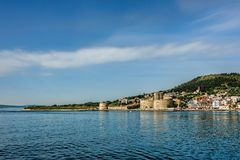 Ancient castle on the seashore under clear blue skies with scatt. Ered white clouds Stock Photos