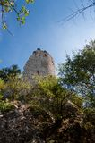 Ancient castle tower in the forest, with blue sky and trees Royalty Free Stock Photos