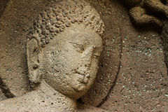 Ancient cave stone carved face at Ajanta Caves. An ancient Buddhist cave stone carved face at Ajanta Caves in Aurangabad, Maharashtra, India, preserved in dark Stock Photo