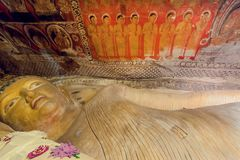 Ancient cave temple with reclining Gautama Buddha figure and painted walls and fresco. DAMBULLA, SRI LANKA - JAN 8, 2017: Ancient cave temple with reclining royalty free stock photos