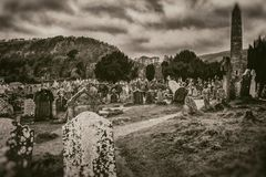 Old ancient Celtic cemetery and tombstones high tower on mountain and stormy sky background in sepia style stock photos
