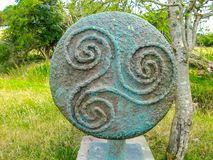 Ancient celtic Triskele or Triple Spiral symbol in bronze. In a green meadow with green trees in the background royalty free stock photography