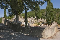 An ancient cemetery with old and new graves in the historic village of Le Poet Laval in the Drome region of the South of France. The tall skyrocket cypress royalty free stock images
