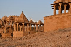 Ancient cenotaph with modern wind mills in bada baag Jaisalmer Rajasthan India Royalty Free Stock Photo