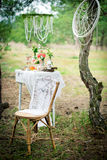 Ancient chair against wedding decoration in style of a shabby shabby chic. Decoration of a wedding photoshoot.  Royalty Free Stock Photos
