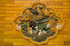 Ancient Chinese Bas-Relief on Orange Brick Wall Royalty Free Stock Images