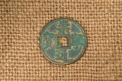 Ancient Chinese bronze coin on old cloth Stock Photos