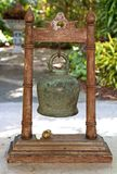 Ancient Chinese Buddhist Temple Bell on Wood Stand. Close up of bronze metal temple bell with wooden carved stand in a garden on a sunny afternoon Royalty Free Stock Photo