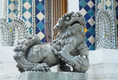 Lion Sculpture in Wat Phra Kaew at Bangkok, Thailand. Ancient Chinese Lion Sculpture or Guardian Lion Holding A Ball in Right Foot at The Entrance or The Inner stock image