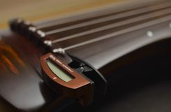 Ancient Chinese musical instrument GuQin with chromatic tuner royalty free stock photo