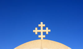 Ancient Christian cross against the blue sky. Stock Images