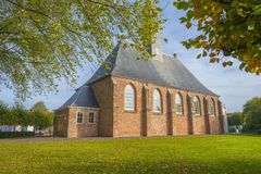 Ancient church in a dutch village in fall colors in autumn in sunlight. In autumn stock photography