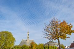 Ancient church in a dutch village in fall colors in autumn in sunlight. In autumn royalty free stock image