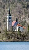 Ancient church with a high Bell Tower on the island on Lake Bled Royalty Free Stock Image