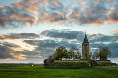 Ancient church tower on a mound. 12th century church tower, also a cemetery, on a mound at Easterwierrum, Netherlands. at sunset Royalty Free Stock Images