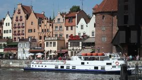 Ancient city with lovely old houses, tourist ship sailing down river, sunny day. Stock footage stock video footage