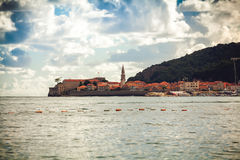 Ancient city with red roofs and defense tower on sea coat Stock Images