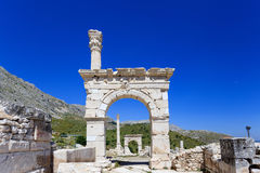 Marble arch and column at ancient city of Sagalassos. Ancient city Sagalassos ruins columns, sculpture and big stones Royalty Free Stock Photo