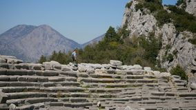 Ancient city Thermessos near Antalya in Turkey. Young woman walking in amphitheater in Pisidian city Thermessos built at an altitude of more than 1000 metres stock video