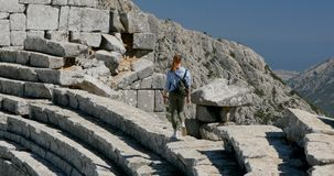 Ancient city Thermessos near Antalya in Turkey. Young woman walking in amphitheater in Pisidian city Thermessos built at an altitude of more than 1000 metres stock footage