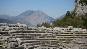 Ancient city Thermessos near Antalya in Turkey. Young woman walking in amphitheater in Pisidian city Thermessos built at an altitude of more than 1000 metres stock video footage