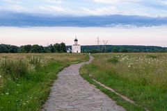 The stone-paved trail through the Bogolubovo meadow towards Church of the Intercession of the Holy Virgin on the Nerl River. Ancient city Vladimir with suburbs Royalty Free Stock Image