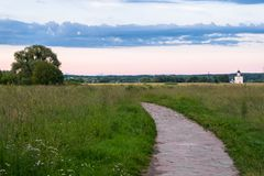 The stone-paved trail through the Bogolubovo meadow towards Church of the Intercession of the Holy Virgin on the Nerl River. Ancient city Vladimir with suburbs Royalty Free Stock Images