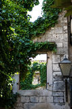Ancient city wall overgrown by Ivy. Seeing through a window in an ancient city wall. the wall is overgrown by ivy. picture taken in Trogir, Croatia Royalty Free Stock Images