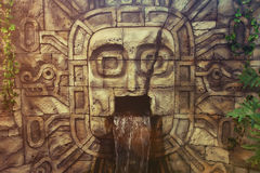 Ancient civilization image of a man in a rock. Ancient artwork on a rock. The head carved from a stone. Water flows from the mouth. Ancient Sumerians, Aztecs Royalty Free Stock Photos