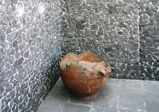 Ancient clay pot against a stone wall Royalty Free Stock Photography