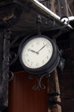 Ancient clock hanging near the wooden building Stock Images