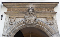 Ancient Coat of Arms above house entrance in Krakow, Poland. Ancient stone Coat of Arms with crones closeup above house entrance in Krakow, Poland Stock Images
