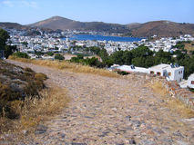 Ancient cobblestone road to greek city. View of the ancient road, greek city, sea and mountains. Island of Patmos Royalty Free Stock Images