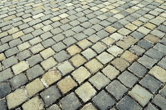 An ancient  cobblestoned city pavement. Made of squares of different color , eternal road which cannot be ruined with time Royalty Free Stock Photos