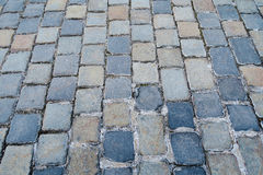 An ancient  cobblestoned city pavement. Made of squares of different color , eternal road which cannot be ruined with time Stock Photography