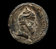 Ancient coin with head on black. Top view Stock Photography