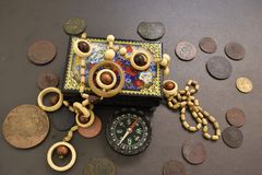 Ancient coins, casket, beads and compass. stock photography