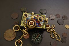 Ancient coins, casket, beads and compass. royalty free stock photos