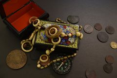 Ancient coins, casket, beads and compass. royalty free stock photography