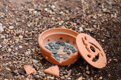 Ancient Coins. Close up view of ancient roman coins laying in a broken terra cotta vase Royalty Free Stock Photo