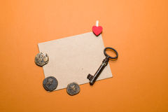 Ancient coins, the key and the envelope on orange background. Royalty Free Stock Photography
