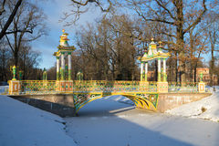 Ancient colourful Chinese bridge in Aleksandrovsky park of Tsarskoye Selo in the cloudy November afternoon. St. Petersburg, Russia Royalty Free Stock Photography