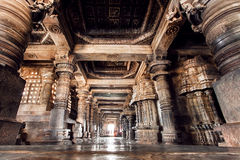 Ancient columns and corridor inside the 12th century stone temple Hoysaleswara, India. Stock Images