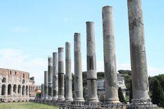 Ancient columns at Piazza di Santa Francesca Romana. Piazza di Santa Francesca Romana with broken columns and Colosseum and Arco di Costantino behind in Rome Royalty Free Stock Image
