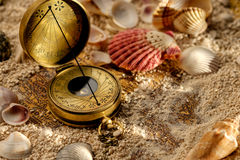 Ancient compass on the sand with seashells Royalty Free Stock Image