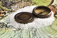 Ancient compass on the world map. Antique compass with metal lid on a color map of the world Stock Image