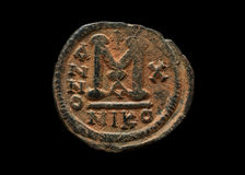 Ancient copper Byzantine coin in red patina. Macro shot royalty free stock photo
