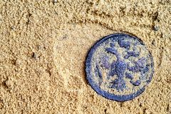 Ancient copper coin with a double-headed eagle covered with sand lying on the sand