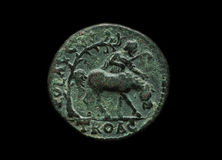 Ancient copper roman coin with horse rider image on it. Isolated on black, close-up shot Royalty Free Stock Images